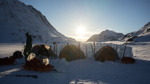 Tents behind the snow wall at sunset, Greenland